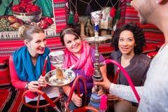 Grupo nas mulheres e nos homens que estão sendo servidos um cachimbo de água no café do shisha foto de stock