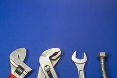 Grupo necessário de ferramentas para encanador em um fundo azul imagem de stock royalty free