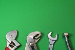 Grupo necessário de ferramentas para encanador em um fundo verde foto de stock