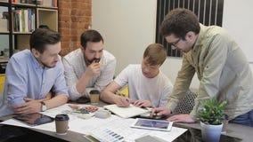 Grupo novo dos empresários que trabalha com projeto startup novo em moderno video estoque