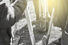 Grupo o equipo de gente que se coloca en la hierba con barajaduras en sus manos listas para el trabajo duro Fotos de archivo libres de regalías
