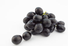 Grupo pequeno das uvas pretas isoladas no fundo branco Fotos de Stock