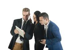 Grupo pequeno de executivos novos que trabalham com tabuleta digital Imagem de Stock