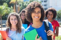 Grupo pequeno de rir estudantes fêmeas caucasianos e latin africanos fotografia de stock