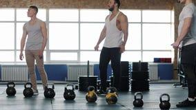 Grupo pequeno dos atletas masculinos durante o exercício no Gym de Crossfit video estoque