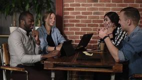 Grupo positivo novo de quatro povos competidos misturados que usam portáteis tabuletas e smartphones que sentam-se no local de tr vídeos de arquivo