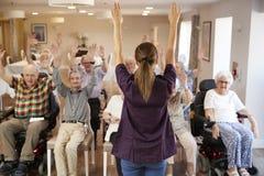 Grupo principal del cuidador de mayores en clase de la aptitud en casa de retiro foto de archivo libre de regalías