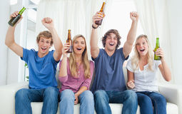 Grupo que anima de amigos que miran la cámara Imagen de archivo libre de regalías
