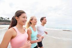 Grupo que corre em movimentar-se da praia fotos de stock royalty free
