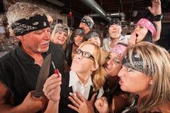 Grupo que faz o divertimento do lerdo com faca Imagem de Stock