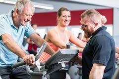 Grupo que gira com o instrutor pessoal no gym fotos de stock royalty free