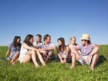 Grupo que se sienta en prado Fotografía de archivo libre de regalías