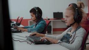Grupo racial mezclado de alumnos elementales en clase del ordenador almacen de video