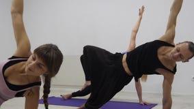 Grupo racial multi de la clase de la yoga que ejercita forma de vida sana en asanas de la yoga del estudio de la aptitud metrajes