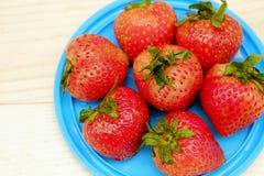 Grupo rojo de la fresa en plato azul Fotos de archivo libres de regalías