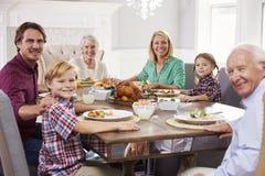 Grupo Sit Around Table Eating Meal de la familia extensa en casa Imagen de archivo