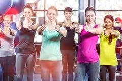 Grupo sonriente apto con los pulgares para arriba Imagen de archivo libre de regalías