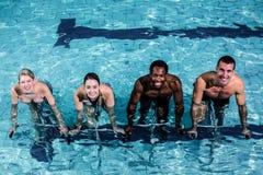 Grupo sonriente apto pedaling en la bici de la natación Imágenes de archivo libres de regalías