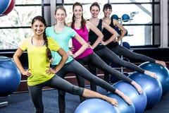 Grupo sonriente apto que hace ejercicio con las bolas del ejercicio Fotos de archivo