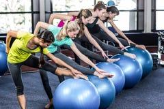 Grupo sonriente apto que hace ejercicio con las bolas del ejercicio Foto de archivo libre de regalías