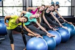 Grupo sonriente apto que hace ejercicio con las bolas del ejercicio Imagen de archivo