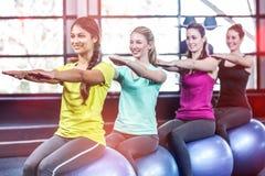Grupo sonriente apto que hace ejercicio con las bolas del ejercicio Imagen de archivo libre de regalías
