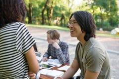 Grupo sonriente de estudiantes jovenes que se sientan y el estudiar Imagen de archivo libre de regalías
