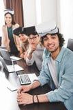 grupo sonriente de socios comerciales multiétnicos con las auriculares de la realidad virtual en la tabla con los ordenadores por imagen de archivo libre de regalías