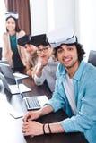 grupo sonriente de socios comerciales multiétnicos con las auriculares de la realidad virtual en la tabla con los ordenadores por foto de archivo