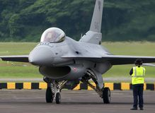 Grupo à terra observando a potência do motor F16 acima Imagens de Stock