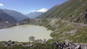 Grupo turístico feliz en el borde de la montaña en el lago del fondo y el pico de montaña almacen de metraje de vídeo