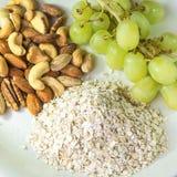 Grupos de alimentos nutritivos de uvas, de nueces mezcladas y de avena adentro al lado de Fotografía de archivo libre de regalías