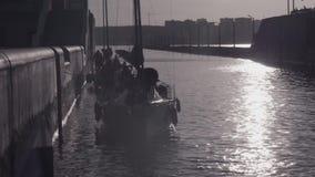 Grupos de dois iate preparados para passar a entrada no fundo da cidade e sob o sol brilhante vídeos de arquivo