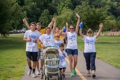 Grupos de la familia con los niños que caminan el 5K Imagen de archivo