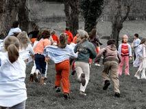 Grupos de muchachos y de muchachas que corren en un parque Fotos de archivo libres de regalías