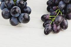 Grupos de uvas azuis maduras frescas em pranchas brancas de madeira velhas fotografia de stock royalty free