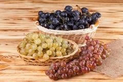 Grupos de uvas azuis maduras frescas na cesta de vime na parte de pano de saco em um contexto textured de madeira Fundo bonito co fotos de stock royalty free