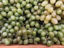 Grupos de uvas frescas verdes no mercado Imagem de Stock