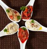 Grupos deliciosos das saladas feitas da pimenta, beringela, tomates no fundo marrom Imagens de Stock Royalty Free