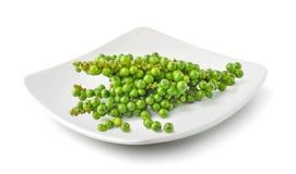 Grupos do grão de pimenta verde fresco em uma placa isolada em b branco foto de stock royalty free