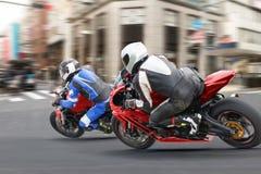 Grupos do motociclista da cidade que rodam uma luz vermelha na cidade Fotografia de Stock Royalty Free