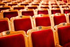 Grupos em um teatro vazio, tomado com foco seletivo e profundidade de campo rasa Assentos vermelhos do vintage vazio com números, imagens de stock royalty free