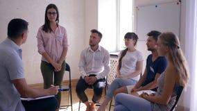 Grupowa terapia, dziewczyna opowiada o problemach i dzieli emocje stoi przed ludźmi zbiory wideo