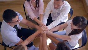 Grupowe terapii, kobiet i mężczyzna sterty ręki jako symbol dla poparcia obsiadania w okręgu na krzesłach, zbiory wideo