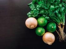 Grupowi organicznie świezi kolendery, cilantro, cebula i wapno, są wewnątrz Zdjęcie Stock