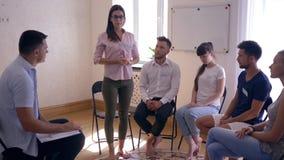 Grupowy psychotherapy, kobieta opowiada o problemach i dzieli emocje stoi przed ludźmi zdjęcie wideo