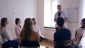 Grupowy psychotherapy, trenerów stojaki przed widownią ludzie na tle biała deska z słowem - problemy zdjęcie wideo
