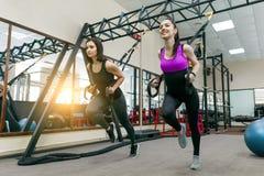 Grupowy szkolenie z pętlami w gym, dwa młodej atrakcyjnej sprawności fizycznej kobiety robi krzyża napadowi z patka systemem Spor fotografia royalty free
