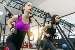 Grupowy szkolenie z pętlami w gym, dwa młodej atrakcyjnej sprawności fizycznej kobiety robi krzyża napadowi z patka systemem Spor zdjęcie stock