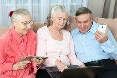 Grupp av äldre folk Grupp av äldre folk som har gyckel, i att meddela med familjen på internet i den bekväma livien royaltyfri fotografi